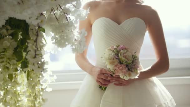 Atraktivní žena ve svatebních šatech s krásné nevěsty kytice