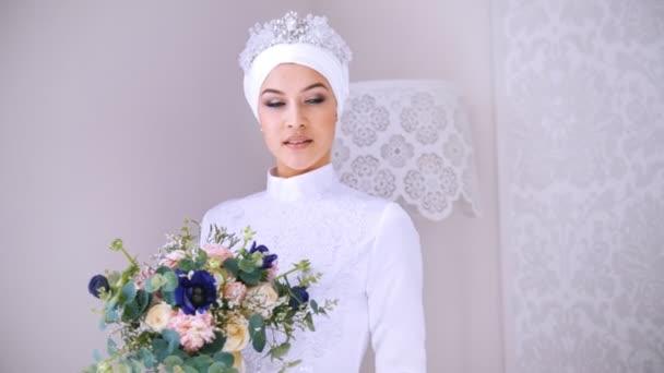 Krásný model v bílé muslimské svatební šaty a svatební čelenka s květinami
