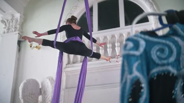 Attractive young woman gymnast performing on aerial silk - exciting acrobatic show, slow-motion