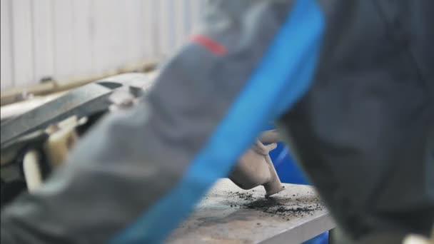 Mechanik muž pracující s autoparts v čerpací stanici