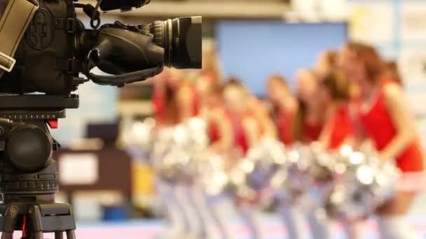 Camera in front of dancing cheerleaders at the karate tornament