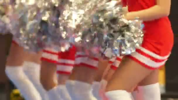 Girls cheerleaders in a red dresses dancing with pompoms