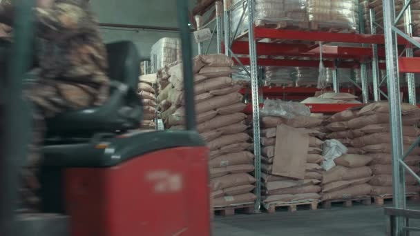 Red loaders transport pallet with boxes on industrial warehouse