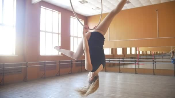 Young acrobatic woman shows flexibility on gymnastic hoop - slow-motion