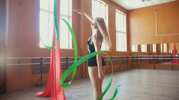 Rhythmic gymnastics - young woman training a gymnastics exercise with a ribbon, slow-motion