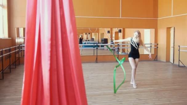 Rhythmic gymnastics - young woman training a gymnastics exercise with a green ribbon