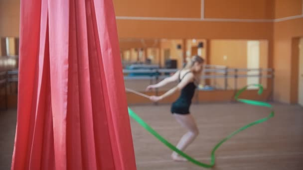 Young attractive woman trains with a green ribbon - gymnastics exercise in studio with mirror - de-focused