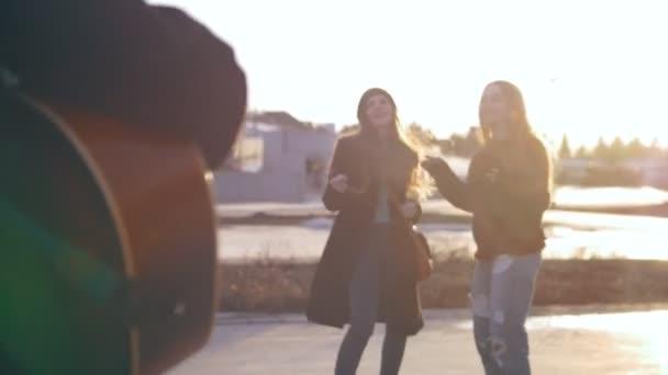 A srác játszik a gitár előtt az utcán a vonzó táncos lányok
