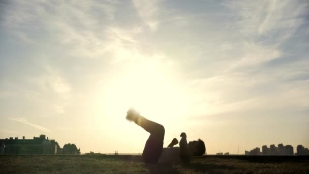Slow-motion - young male Parkour tricker jumper performs amazing flips in front of the sun