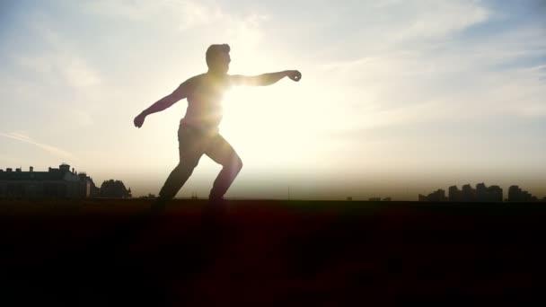 Pomalý pohyb - mladý muž Parkour tricker skokan provádí úžasné vyletí před slunce