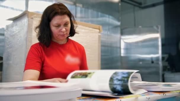 Zaměstnankyně typografie obracet stránky tištěného časopisu