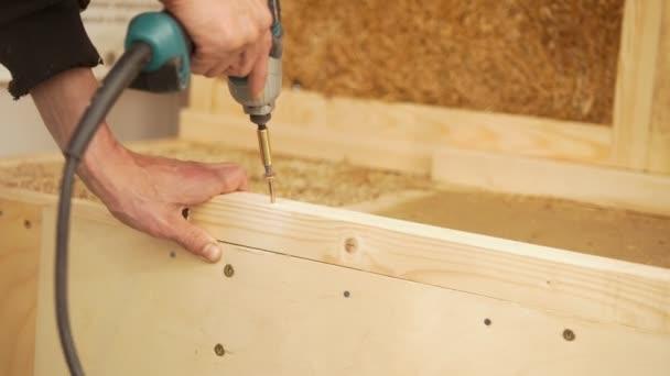 Ruka muže s šroubovák rotující šroub na dřevo