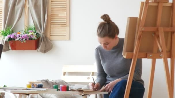 Female painter draws sketches of naked woman in a drawing studio