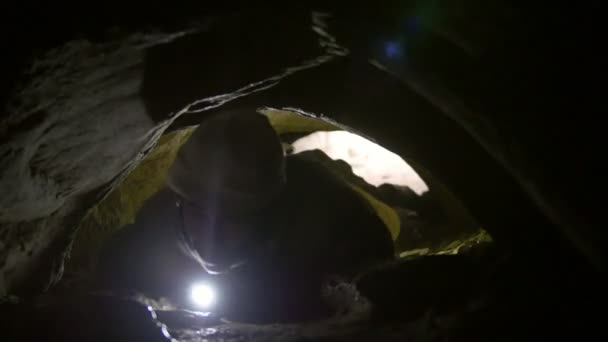 Young man crawls through narrow hole in cave with flashlight in his hand