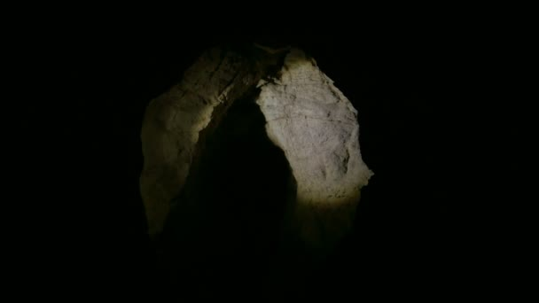 Young female speleologist climbing into the dark narrow cave explores the cave with flashlight