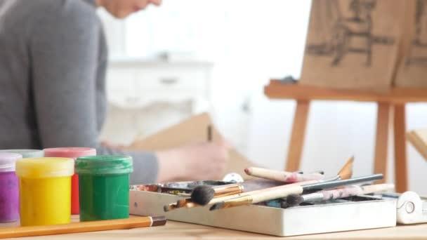 Művészeti kellékek és festékek előtt teljesítő művészeti Etűd witn meztelen modell painer