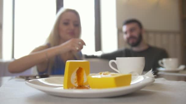 Sladký zákusek před pár sedí v kavárně pije kávu a směje se