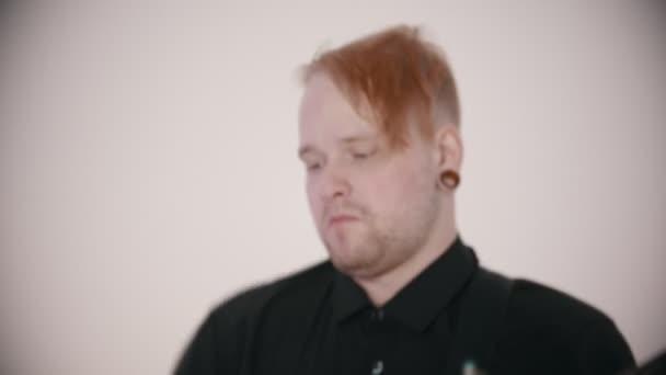 Hudební skupina hrající píseň - muž kytarista se zástrčkami v uších a bubeník hraje jejich role
