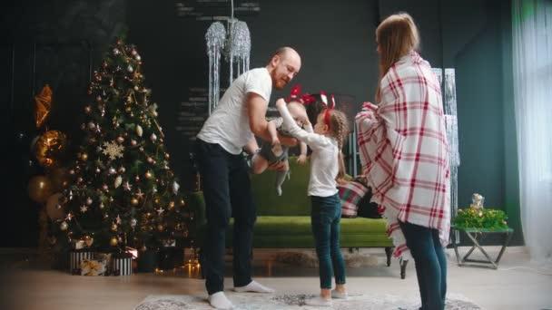 Neujahr - Mama und Papa tanzen mit ihren Kindern am Weihnachtsbaum - lustige Stirnbänder auf den Kinderköpfen