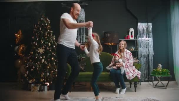 Karácsonyi koncepció - apa és lánya táncol a nappaliban - anya egy babával nézi őket és mosolyog