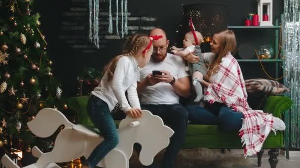 Weihnachtsfamilienkonzept - Papa sitzt im Handy - Tochter nimmt das Telefon und Baby die Brille weg