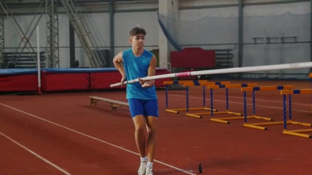 Pole vault training - a young man in blue shirt breathing in and out and starts running up before jumping