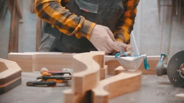 Tesařství v interiéru - muž dřevorubec řezání lepicí pásky - dílna