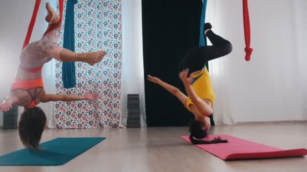 Légi jóga - két nő gyakorol - fejjel lefelé lógnak és forognak - jól érzik magukat