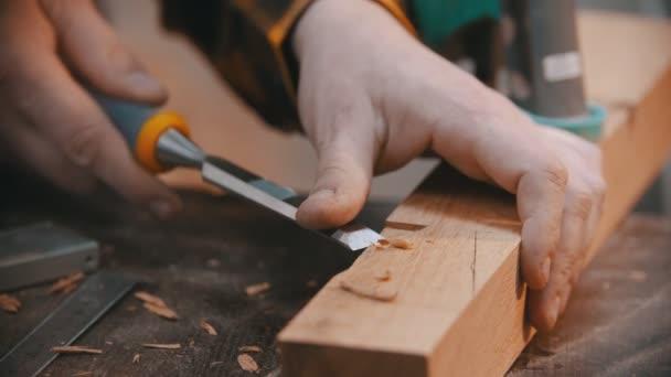 tesařství - dřevorubec vyřezávající výklenek na dřevěném bloku dlátem - muž pracující bez rukavic