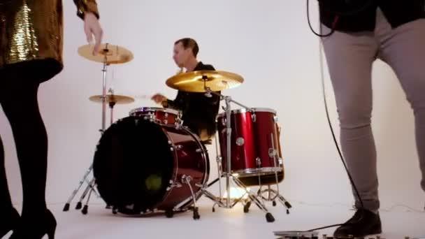 Emocionální hudební kapela hrající píseň ve světlém studiu - natáčení videoklipu