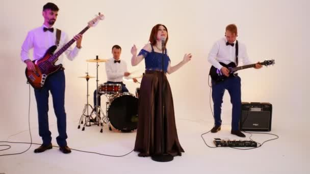 Hudební skupina čtyř dospělých lidí hrajících ve studiu písničku