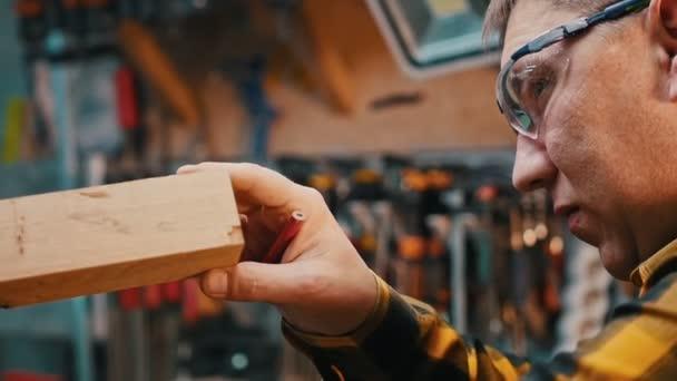 Truhlářský průmysl - muž dřevorubec stojící v dílně a kontrolovat detailní roztříštěné nedostatky