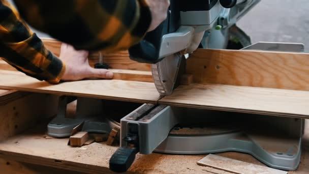Tesařský průmysl - dřevorubec řezající kus dřeva velkou kruhovou pilou v dílně