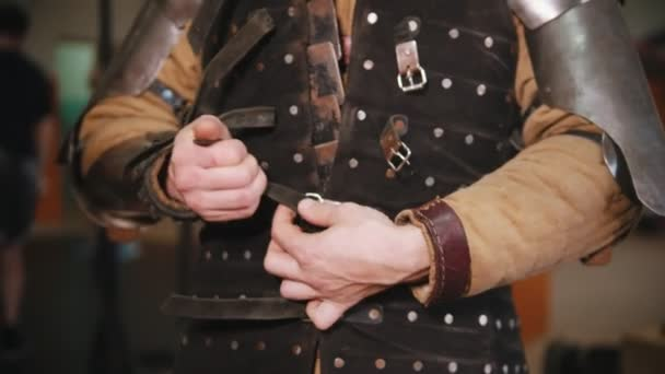 Men putting on a knight armour in the dressing room - putting on a jacket