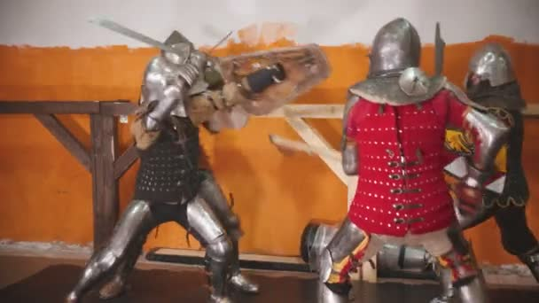 Four men knightes having a training fight indoors