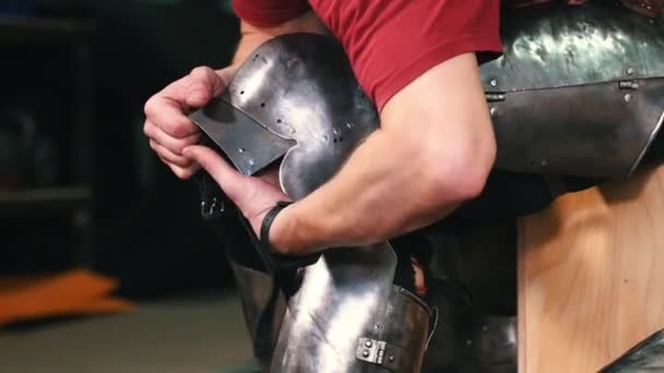 Knights training - a man sets on a metal protection armour on his legs