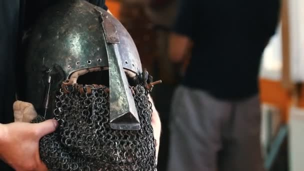 Knights training - a man holding a protective iron helmet