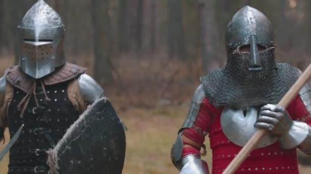 Zwei Männer laufen in voller Rüstung mit Waffen in der Reihe durch den Wald