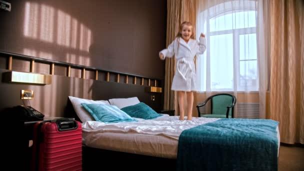 ein kleines Mädchen springt auf das Bett des Hotelzimmers