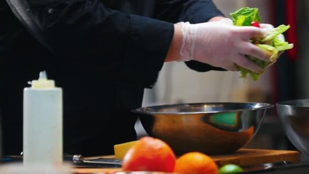 Küche - Koch überträgt Gemüse aus einer Schüssel
