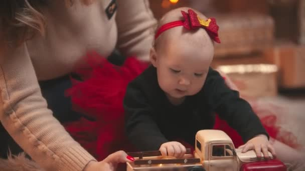 Christmas - a little baby girl playing with a toy car