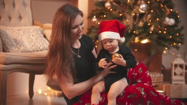 Vánoční koncept - Usmívající se žena hraje se svým malým synkem - dítě drží zlaté vánoční míč