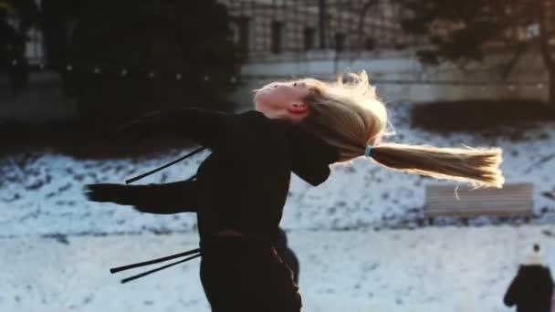 Mladá žena s vlnitými vlasy točícími se kolem sebe na kluzišti