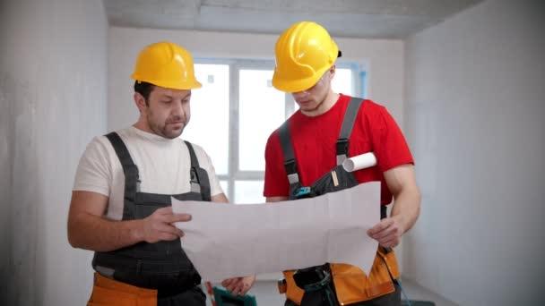 Apartman javítás - két férfi munkás megvitatása egy lakás terv munka előtt, és rámutatva a falakra
