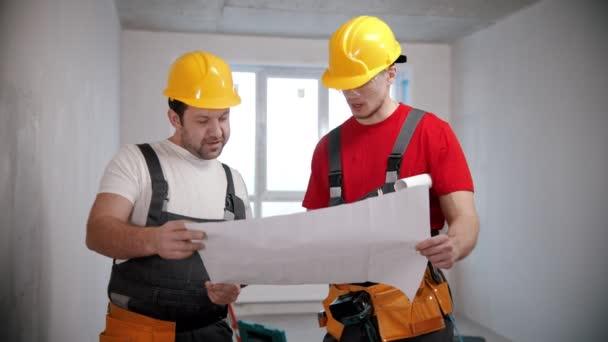 Wohnungsreparatur - zwei Männer besprechen einen Wohnungsplan und zeigen auf die Wände