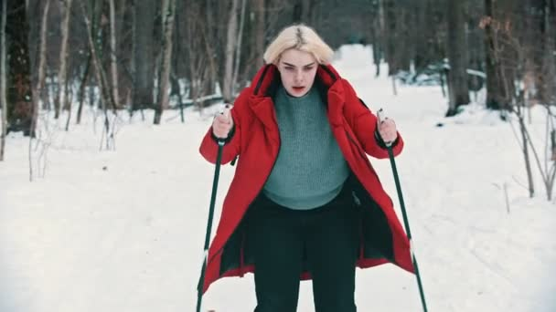 A young blonde woman in red down jacket skiing with an effort in the forest
