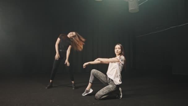 Dvě mladé ženy se zahřívají před tancem ve studiu