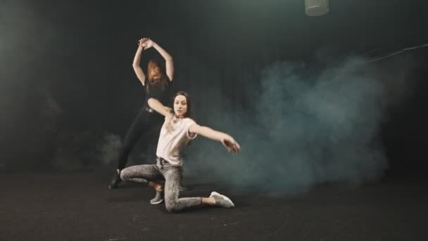 zwei junge Frauen, die zufällig im Studio tanzen