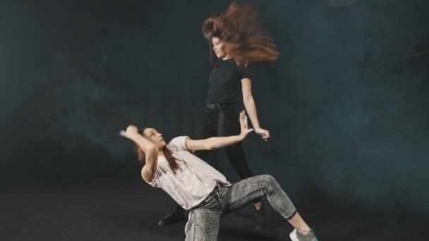 zwei junge Frauen beim Tanzen im dunklen Studio