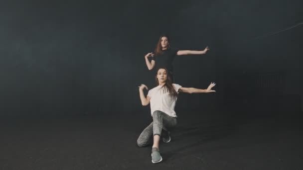 Two young women training a synchronous dance choreography in dark studio